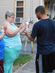 Mary Stache and Clint Reed work to relight candles blown out by the wind Friday, Aug. 31, 2018, during a vigil promoting safety on Garber Street. The Chambersburg street has seen at least two gun-related incidents in just over a year, one of them a fatal shooting, as well as fights and reckless driving incidents.