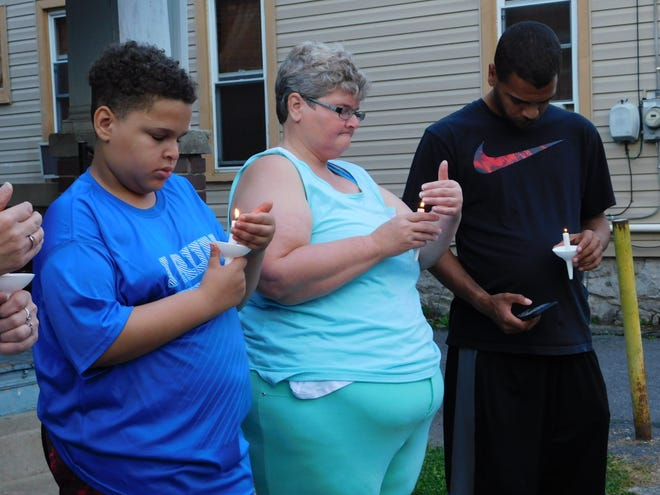 Chris Stache, Mary Stache and Chris Reed protect their candles from the wind Friday, Aug. 31, 2018, during a vigil promoting safety on Garber Street. The Chambersburg street has seen at least two gun-related incidents, as well as fights and reckless driving incidents, residents say, in just over a year.