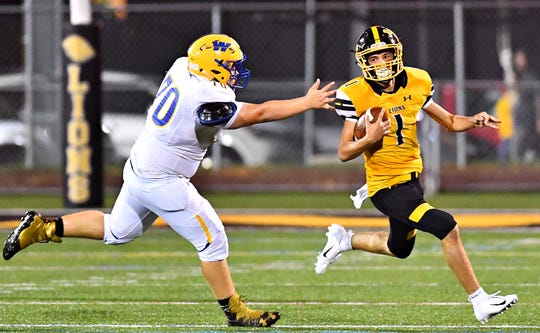 Red Lion's Randy Fizer evades Waynesboro defender Xavier Rhyne in the Lions' 48-14 win over the Indians.
