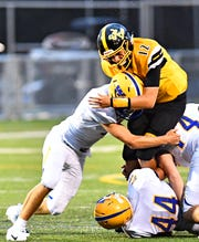 Red Lion quarterback Zach Mentzer tries to break loose from multiple Waynesboro tacklers in the Lions' 48-14 win.