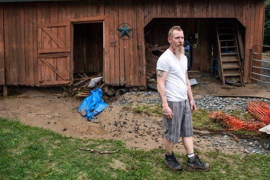 Mike Bray, who moved into his home at 4973 Lees Lane in Hellam Township, poses for a photo in front of his barn that was destroyed by Friday night flooding, Saturday, September 1, 2018. 'It's complete devastation, man,' Bray said. He and his fiancŽ were planning on getting married on the property soon.