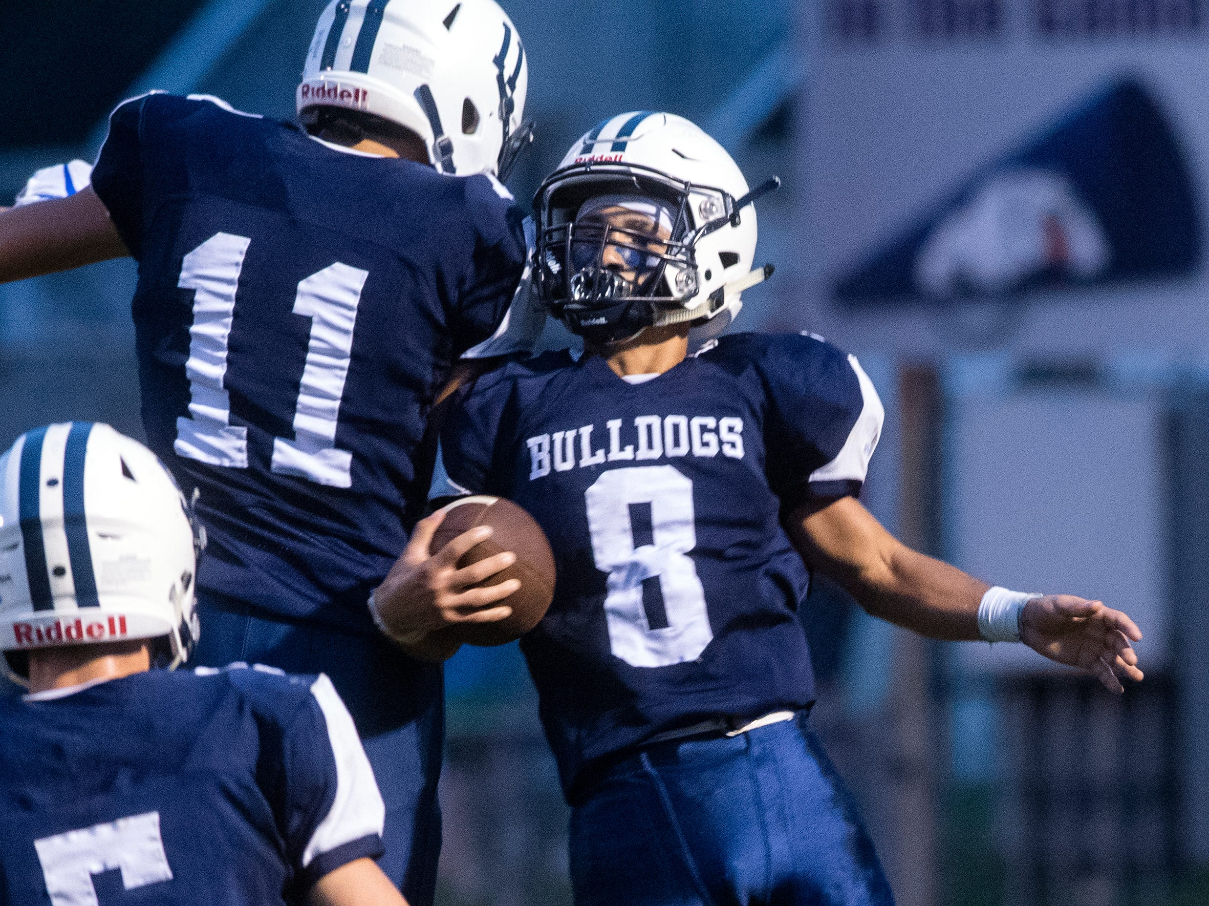 West York's Shane Kauffman (8) celebrates a touchdown with teammate Jose Pena (11), Friday, Aug. 31, 2018. The Shippensburg Greyhounds beat the West York Bulldgos, 21-14.