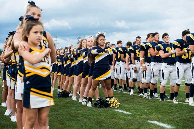 Littlestown cheerleaders and football players salute the flag before Friday's game.