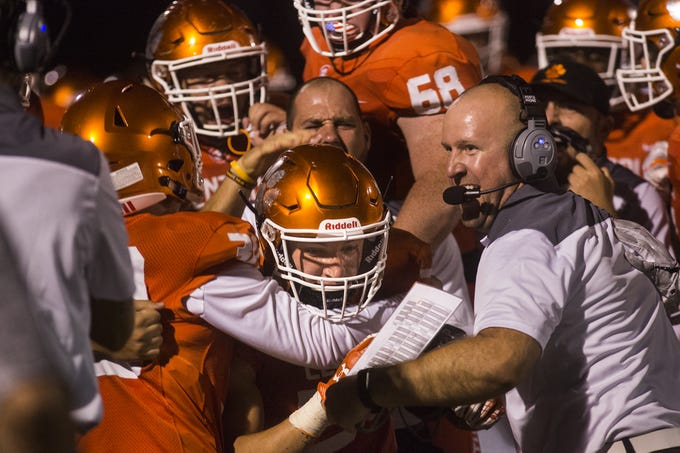 Central York's Anthony Tsirigos, center, is swarmed by coaches and players on the sideline after an interception. Central York defeats Cumberland Valley 31-14 in football at Central York High School in Springettsbury Township, Friday, August 31, 2018.