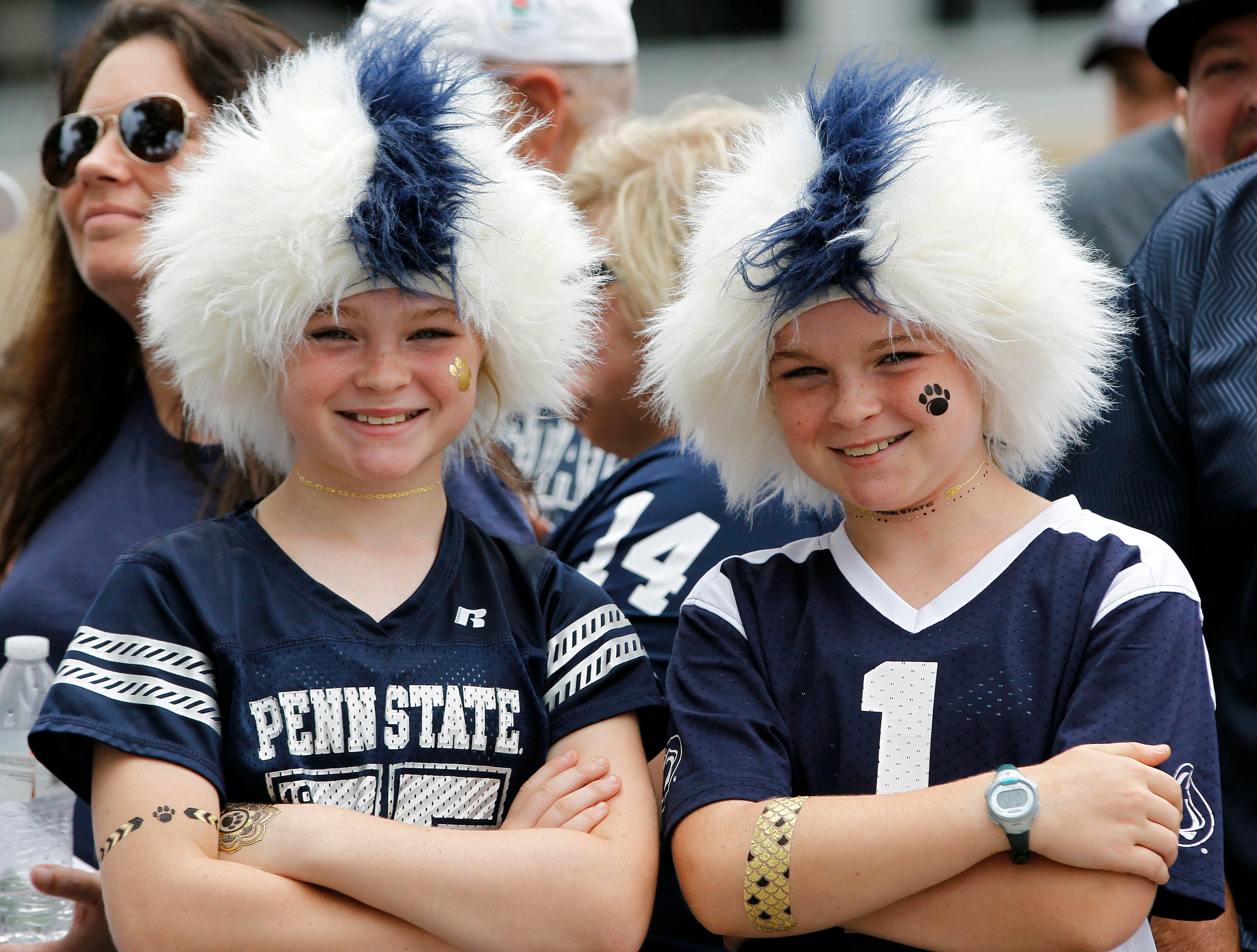 Penn State fans Alexis Stoudt, 11, left, and her twin sister Ainsley Stoudt, 11, both from State College, Pa., wait for the team to arrive at the stadium to take on Appalachian State in an NCAA college football game in State College, Pa., Saturday, Sept. 1, 2018. (AP Photo/Chris Knight)