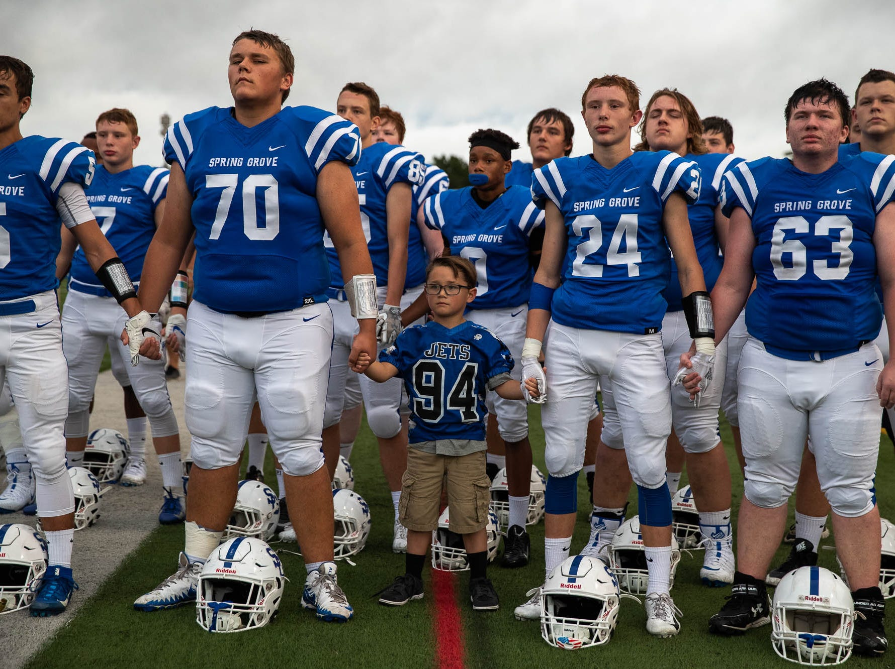 Spring Grove's John Halaj (70) and Montgomery Jarvis (24) hold hands with ballboy Josh Forry, 8, as the National Anthem plays before a football game between Muhlenberg and Spring Grove, Friday, Aug. 31, 2018, in Spring Grove.