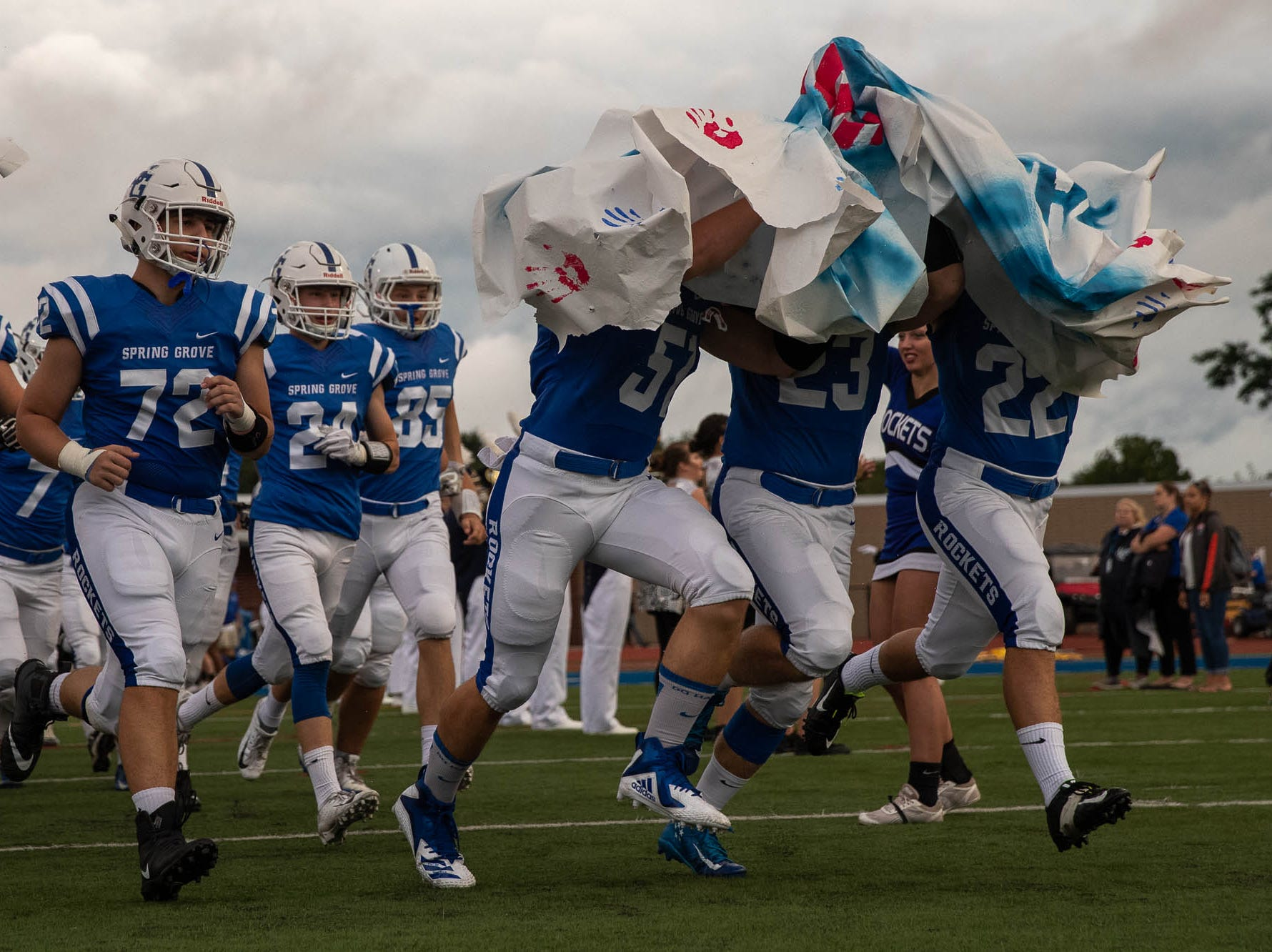 Spring Grove's Riley Merrill(51), Eric Glass Jr. (23), and Braden Brandt (22) get caught in the banner as they burst through it while entering the field for a football game between Muhlenberg and Spring Grove, Friday, Aug. 31, 2018, in Spring Grove.
