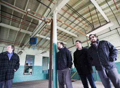 Who is behind these renovations? In 2012, York High grads Patrick Dahlheimer, second from left, Chad Gracey and Chad Taylor, members of the rock bank Live, talked about investing in their hometown by forming a company that would run fiber optic cable from New York through York. 210 York Street would be the headquarters. They are seen inside the building, before renovations, with Michael Helfrich, now York's mayor.