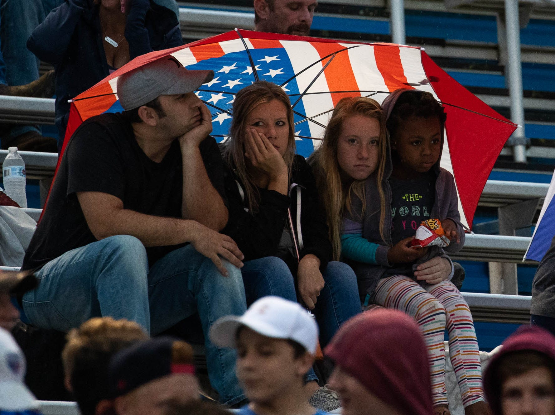 Spring Grove fans watch under an American flag umbrella during a football game between Muhlenberg and Spring Grove, Friday, Aug. 31, 2018, in Spring Grove.