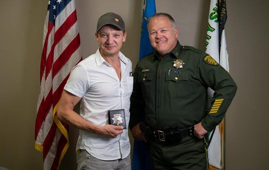 Actor Jeremy Renner poses for a photo with Chief Deputy Tom Green, who supervises special operations and detention for the Washoe County Sheriff's Office, on Aug. 30, 2018.