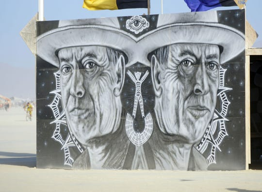 A mural of Burning Man founder Larry Harvey looks out from the center camp area. Harvey died this spring following a stroke.