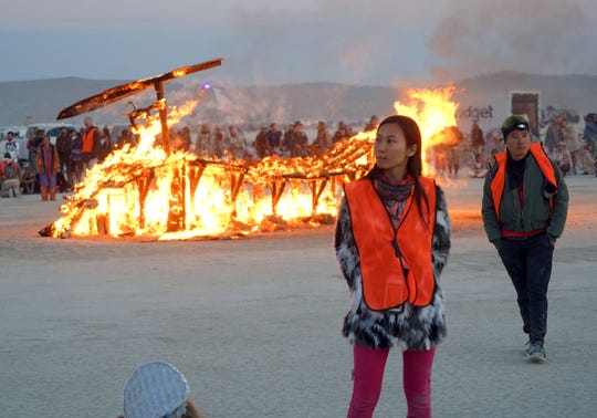"A pair of safety wardens guard a burning piece of art at Burning Man. Event organizers have increased the number of wardens at large ""burns"" to prevent anyone from running to the flames."