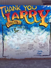A mural on the wall at Burning Man's Center Camp holds memories written by attendees remembering founder Larry Harvey.