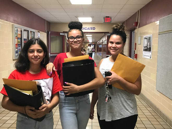 Greece students and mother pick up free school supplies. Valeria Cotarelobrito, left, Dalilah Addamson, center, and Darlyn Harris.