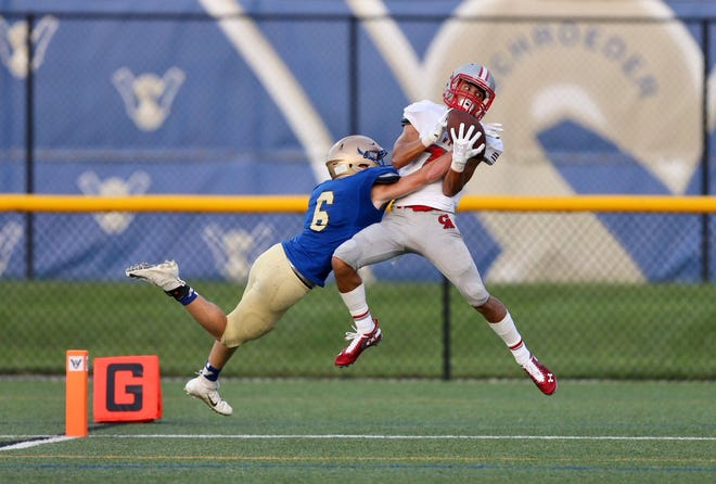Canandaigua's Mitchell Pfeiffer hauls in this pass over Webster Schroeder's Dominik Ferrante to give the Braves a 14-0 lead over Webster Schroeder early in the second quarter of Friday night's season opener at Webster.