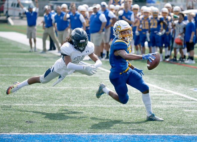 Irondequoit's Jadon Turner scores running past Eastridge's Isaiah Rivera to give the Eagles a 7-0 lead in the first quarter at Irondequoit High School.