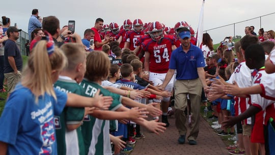 Fairport coach Marc Vitticore leads the Red Raiders onto the field for the regular season opener.