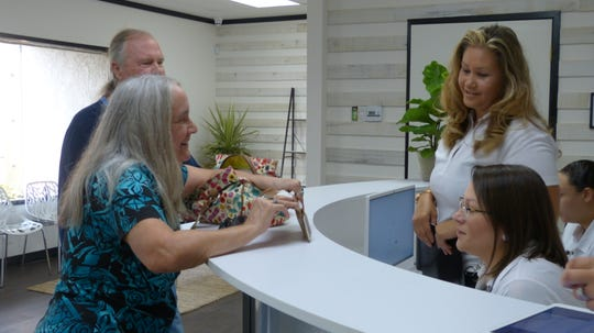 Kathy Nihart and her husband Gary Nihart, the first clients at the Synergy store, checked in at the front counter.