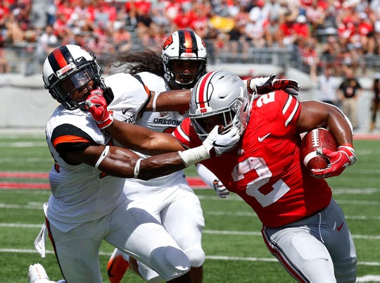 Sep 1, 2018; Columbus, OH, USA; Ohio State Buckeyes running back J.K. Dobbins (2) gets face masked by Oregon State Beavers safety Jeffrey Manning Jr. (15) during the first quarter at Ohio Stadium. Mandatory Credit: Joe Maiorana-USA TODAY Sports