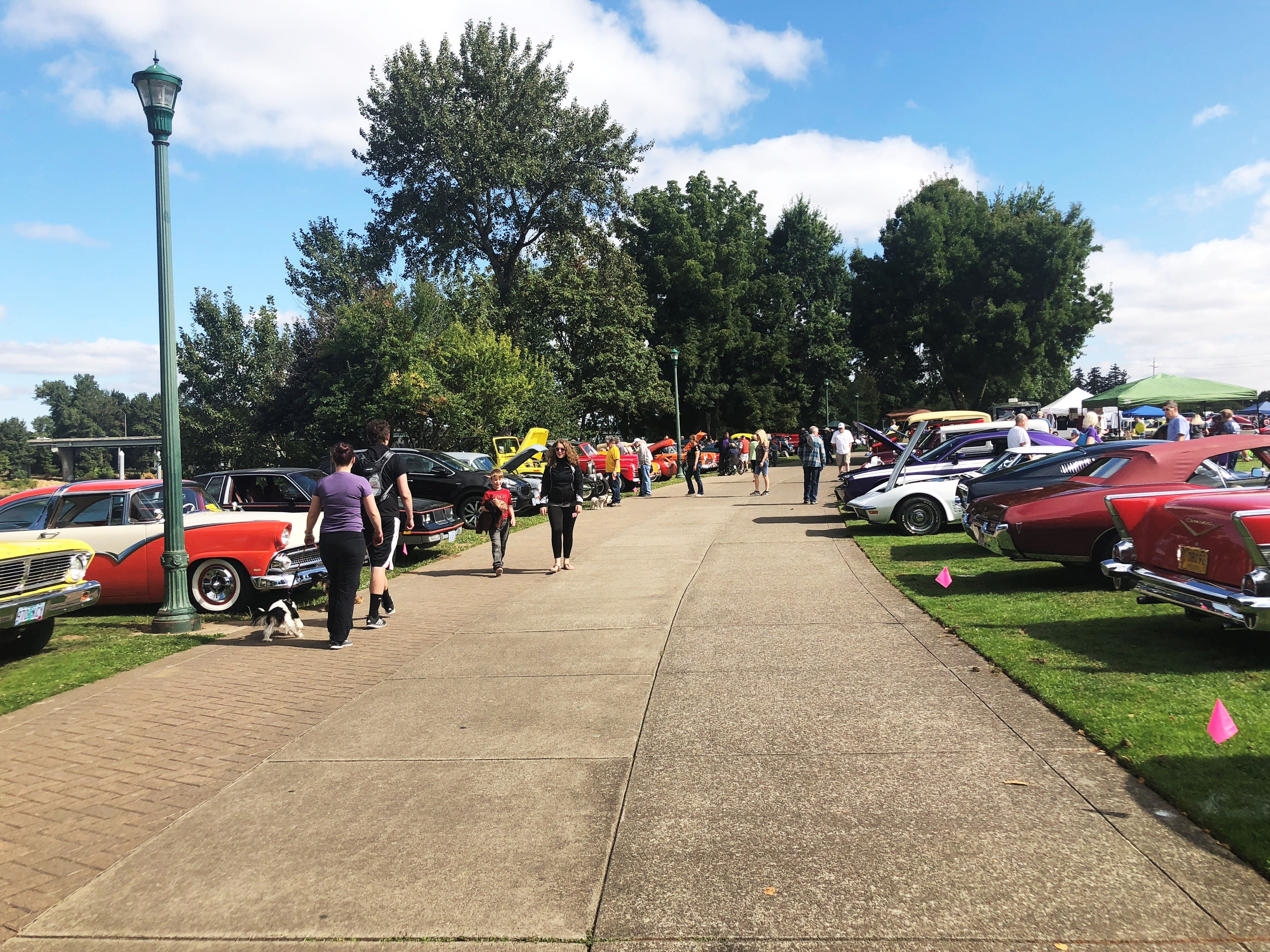 Spectators walk through two rows of cars at the 27th Annual Carousel Cruise at Riverfront Park in Salem on Saturday, Sept. 1.