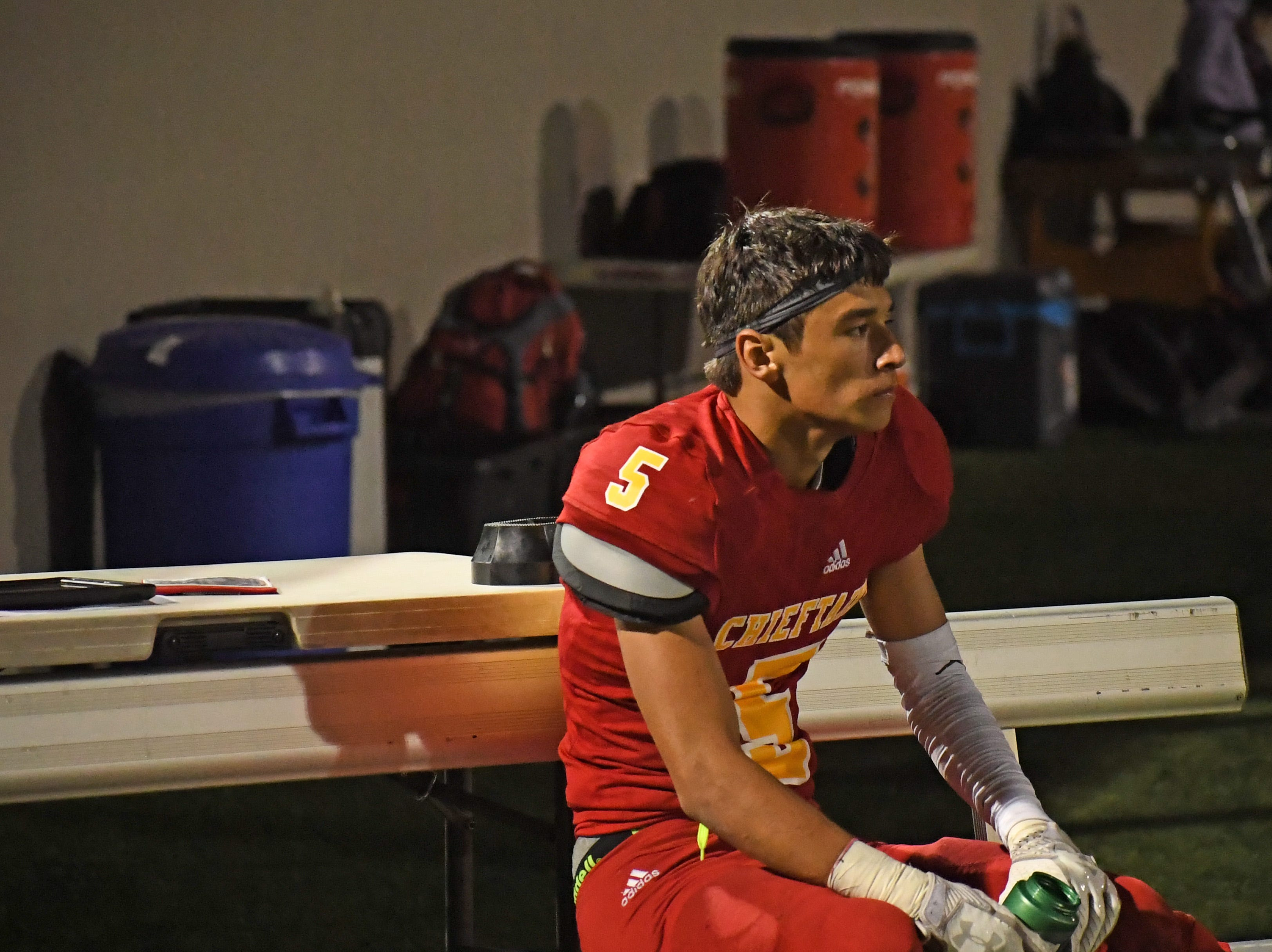 Palma senior Matt Morales (5) rests on the bench after he and the Palma defense forced a three and out.