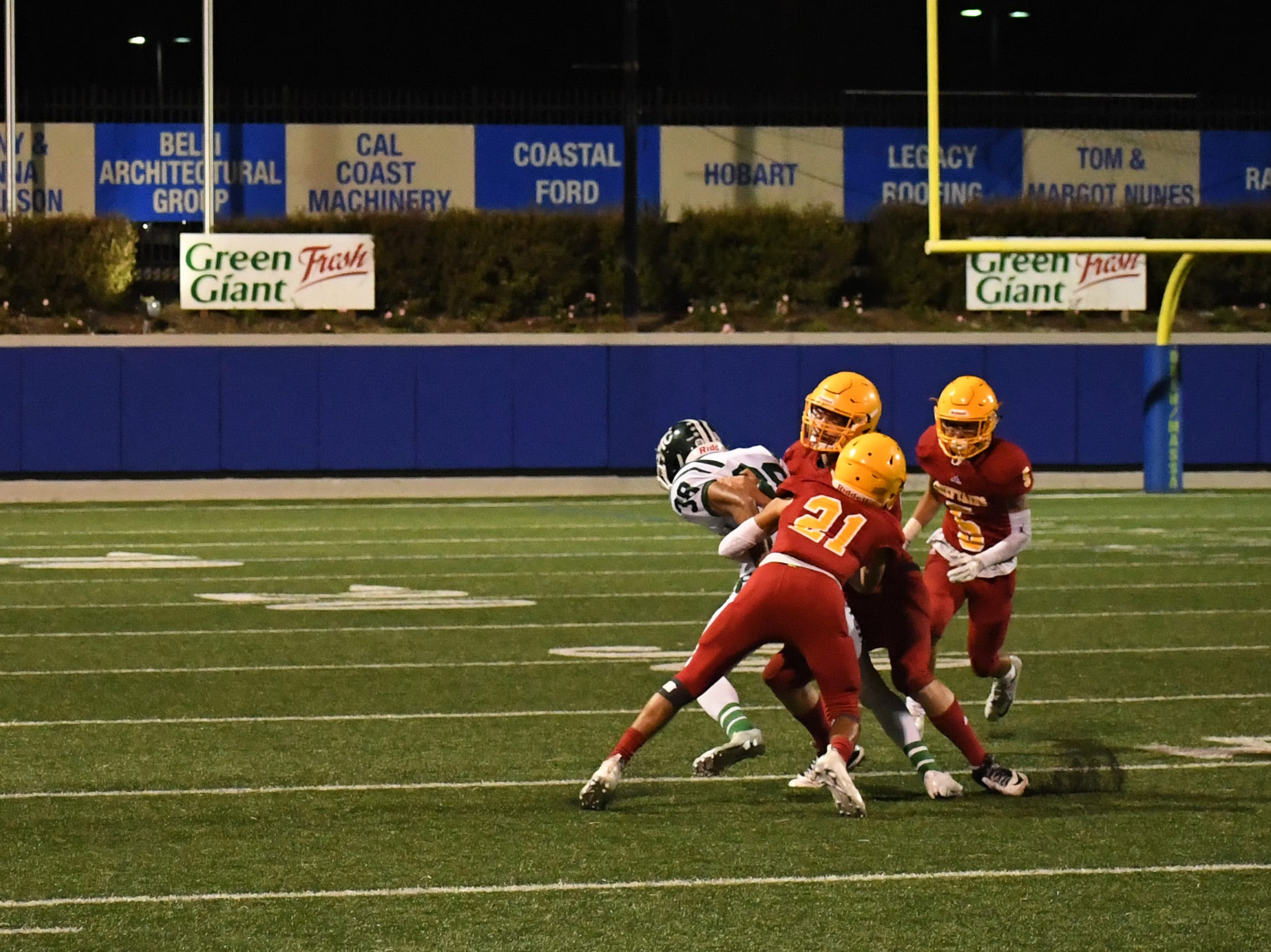 Palma defenders Adam Pantoja (21) and Dane Golden tackle a Sacred Heart Cathedral wide receiver.
