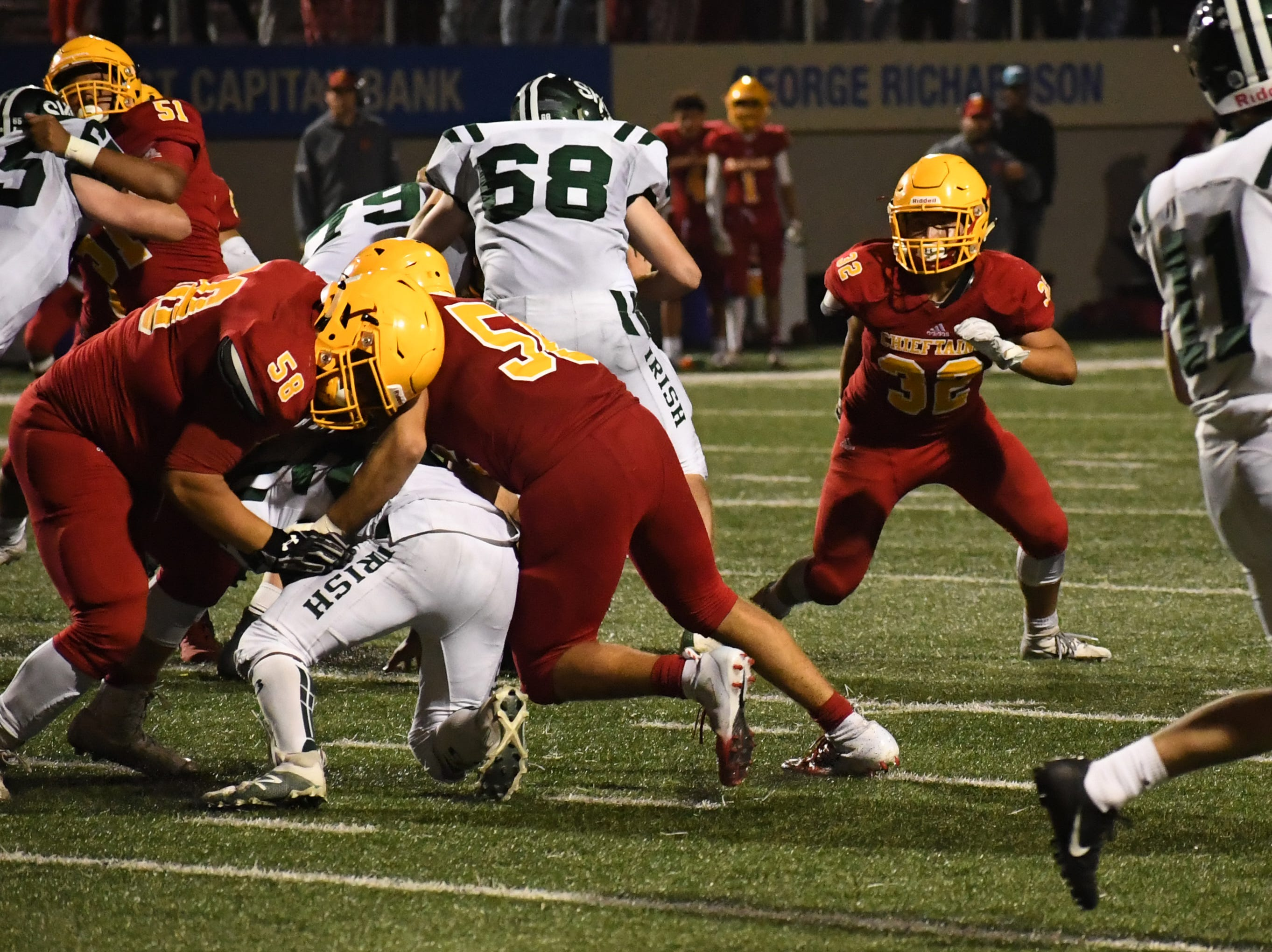 Palma defenders Daniel Cabrera (58) and Jose Velasquez (56) tackle a Sacred Heart Cathedral running back.