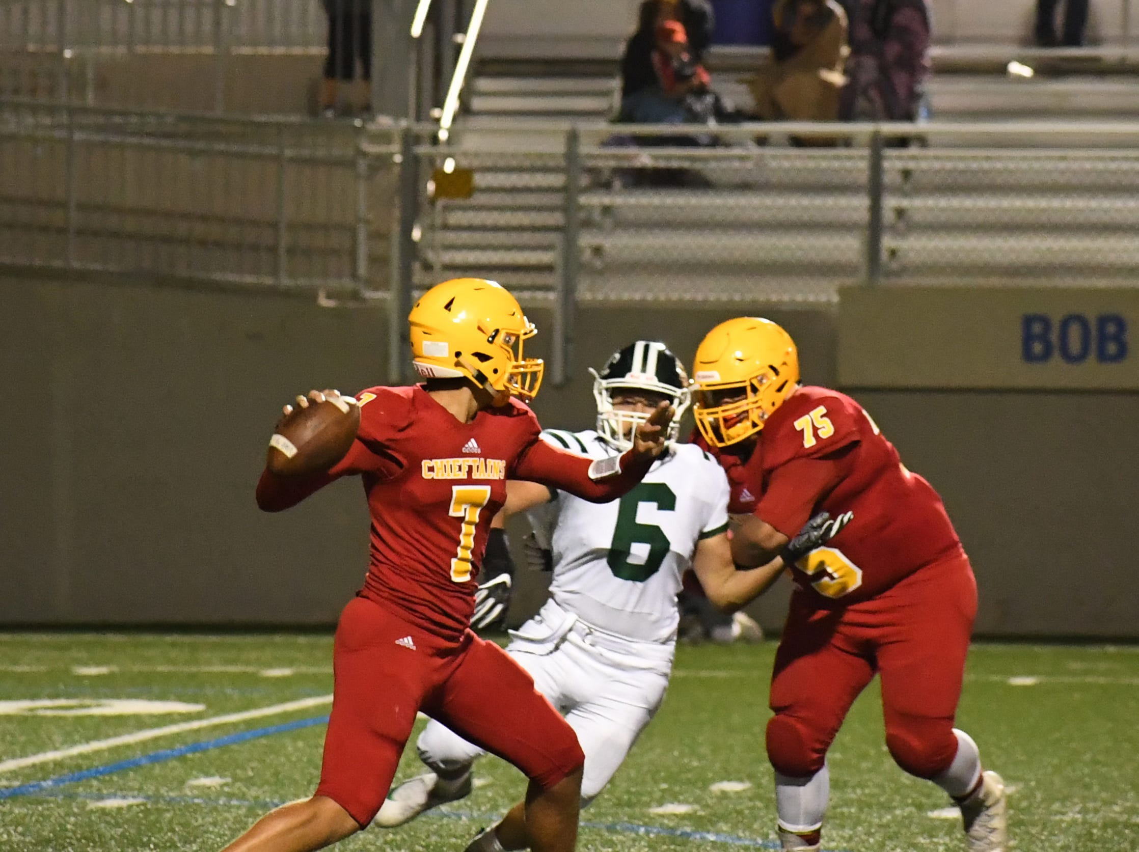 Palma senior quarterback Grant Sergent (7) has to throw the ball to avoid pressure from Sacred Heart Cathedral's defense.