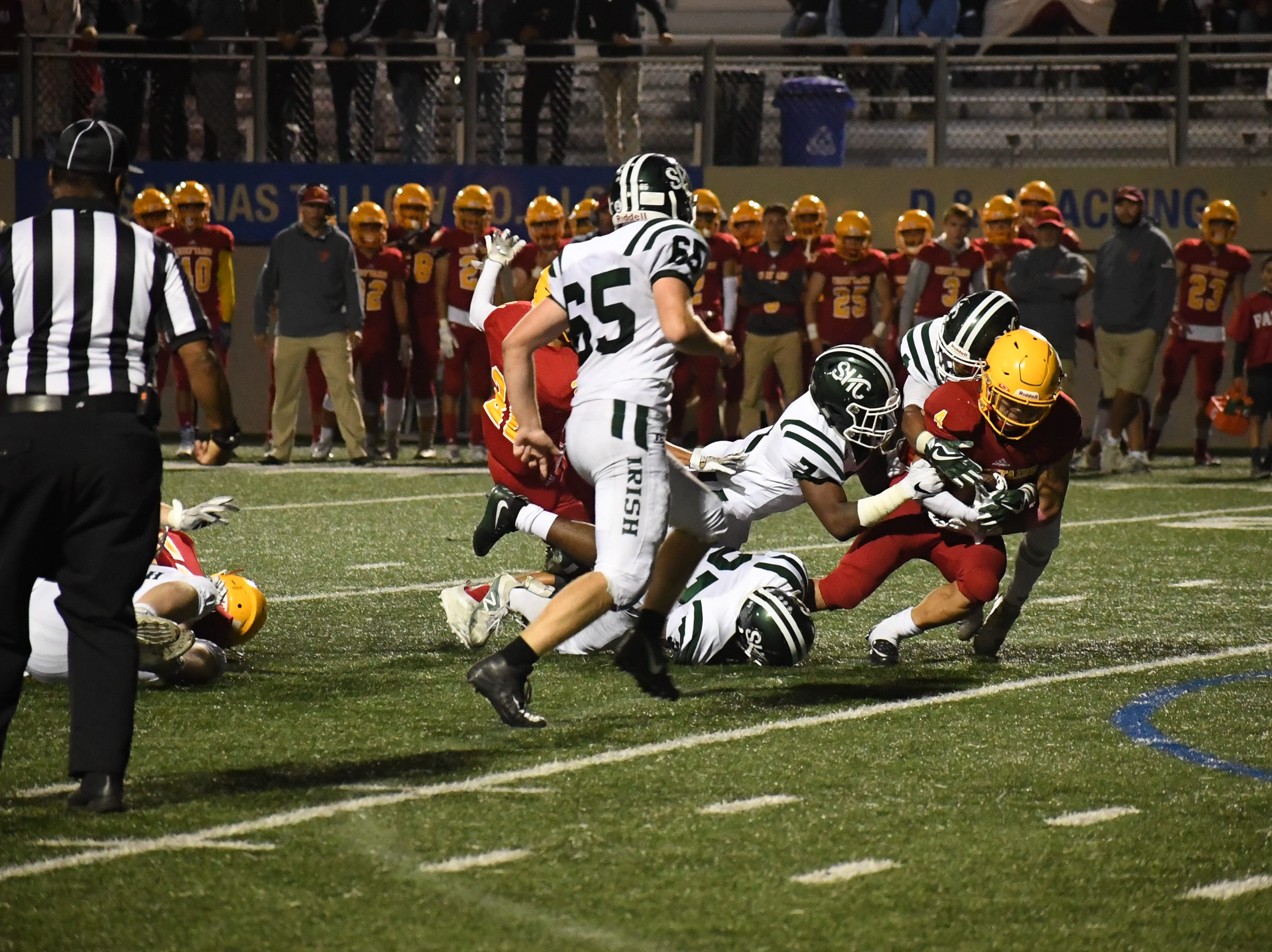 Palma running back Anthony Villegas (4) fights for extra yards against the Sacred Heart Cathedral defense.