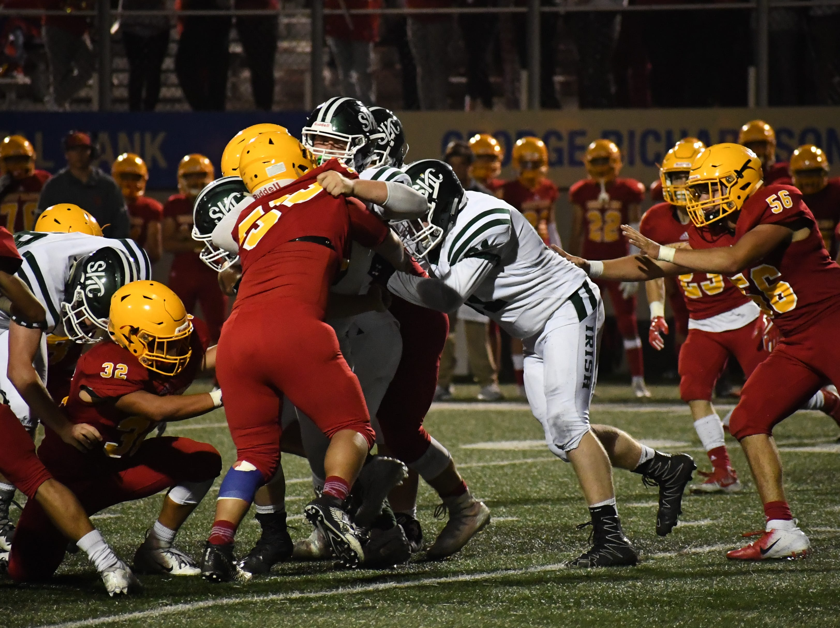 Palma defenders Diego Guajardo (32) and Jose Velazquez (56) wrap up a Sacred Heart Cathedral running back.