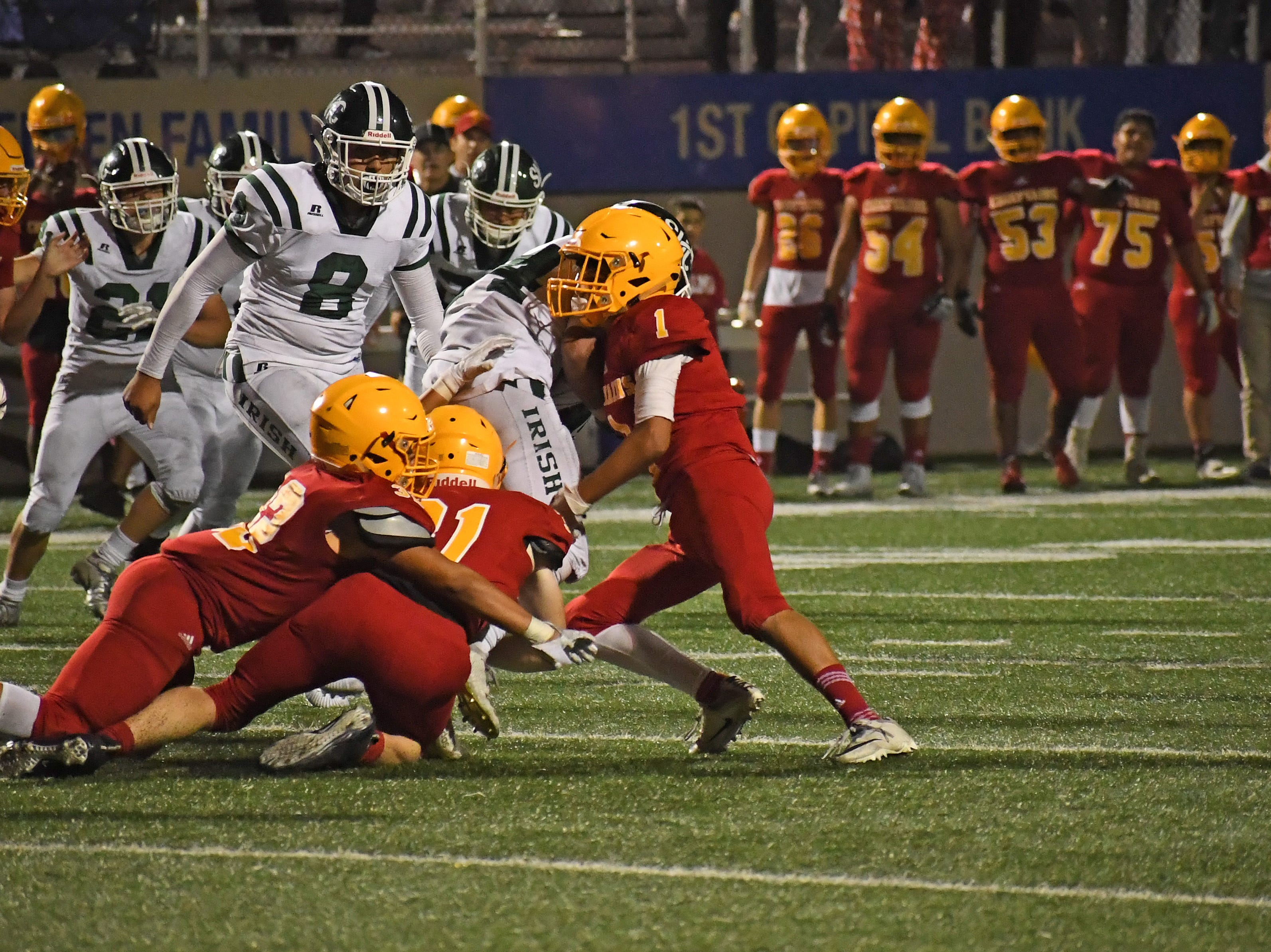 Palma defenders Brent Eastman (31), Diego Guajardo (32) and Abel Escobar (1) rally to take down a Sacred Heart Cathedral running back.