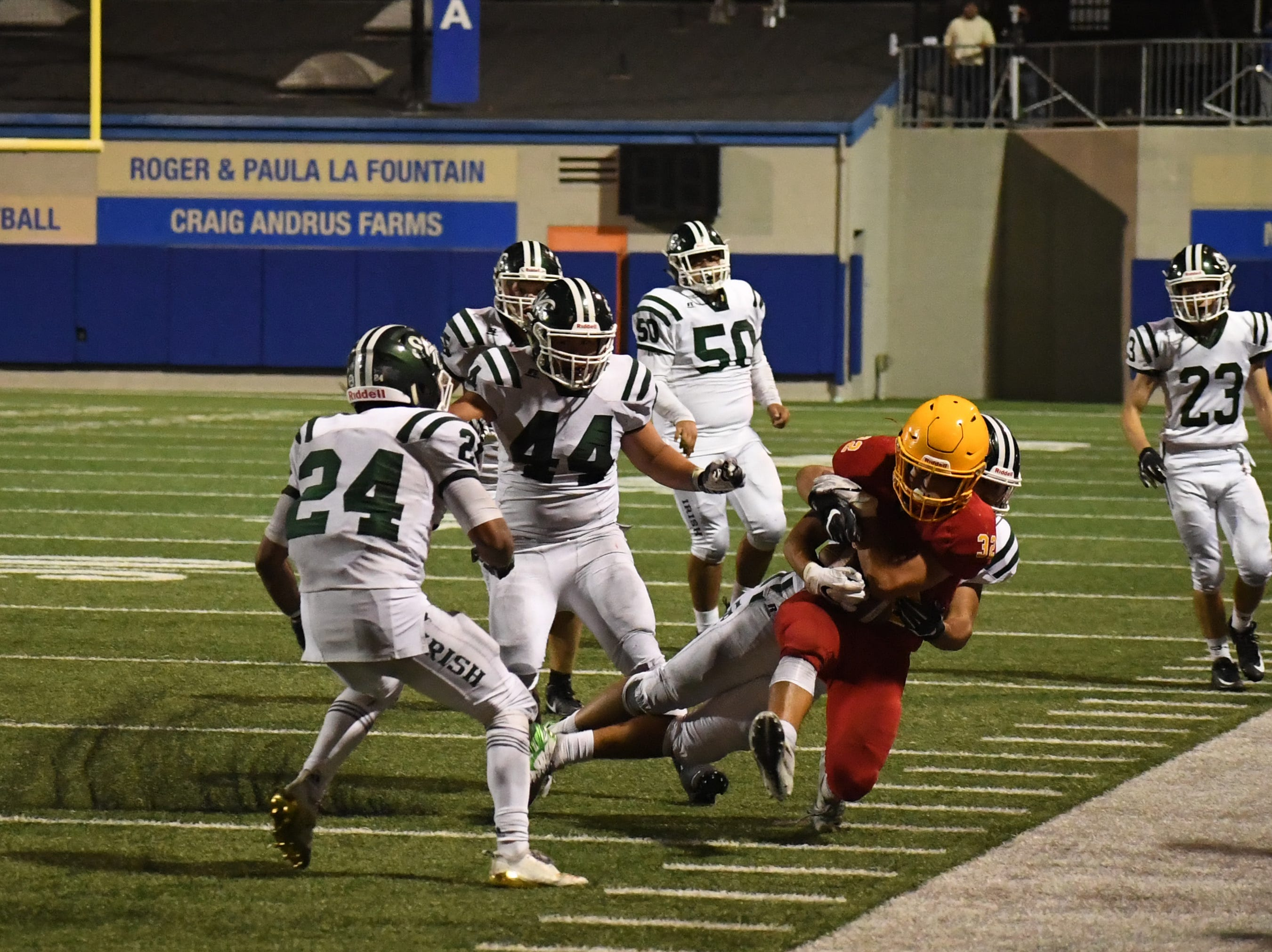 Palma senior Diego Guajardo (32) is tackled along the visitors' sideline in the fourth quarter.