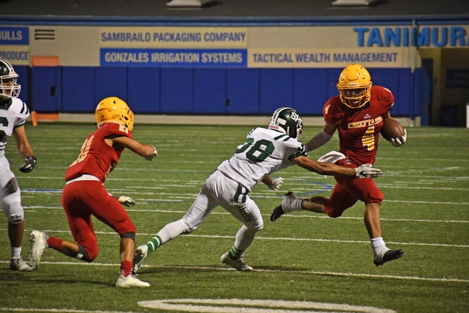 Palma junior running back Anthony Villegas (4) stiff arms a defender out of the way on his way to a 37-yard touchdown.