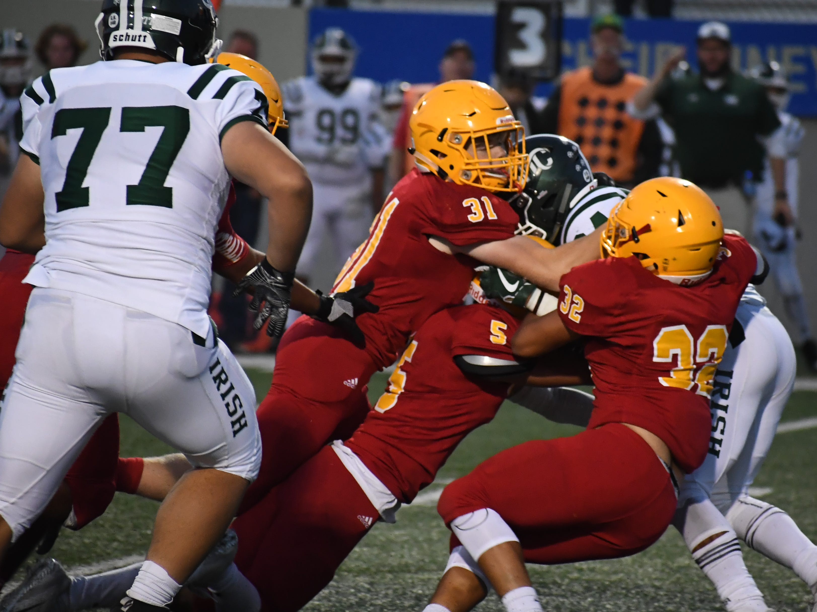 Palma junior Brent Eastman (31) and seniors Matt Morales (5) and Diego Guajardo (32) take down a Sacred Heart Cathedral running back.