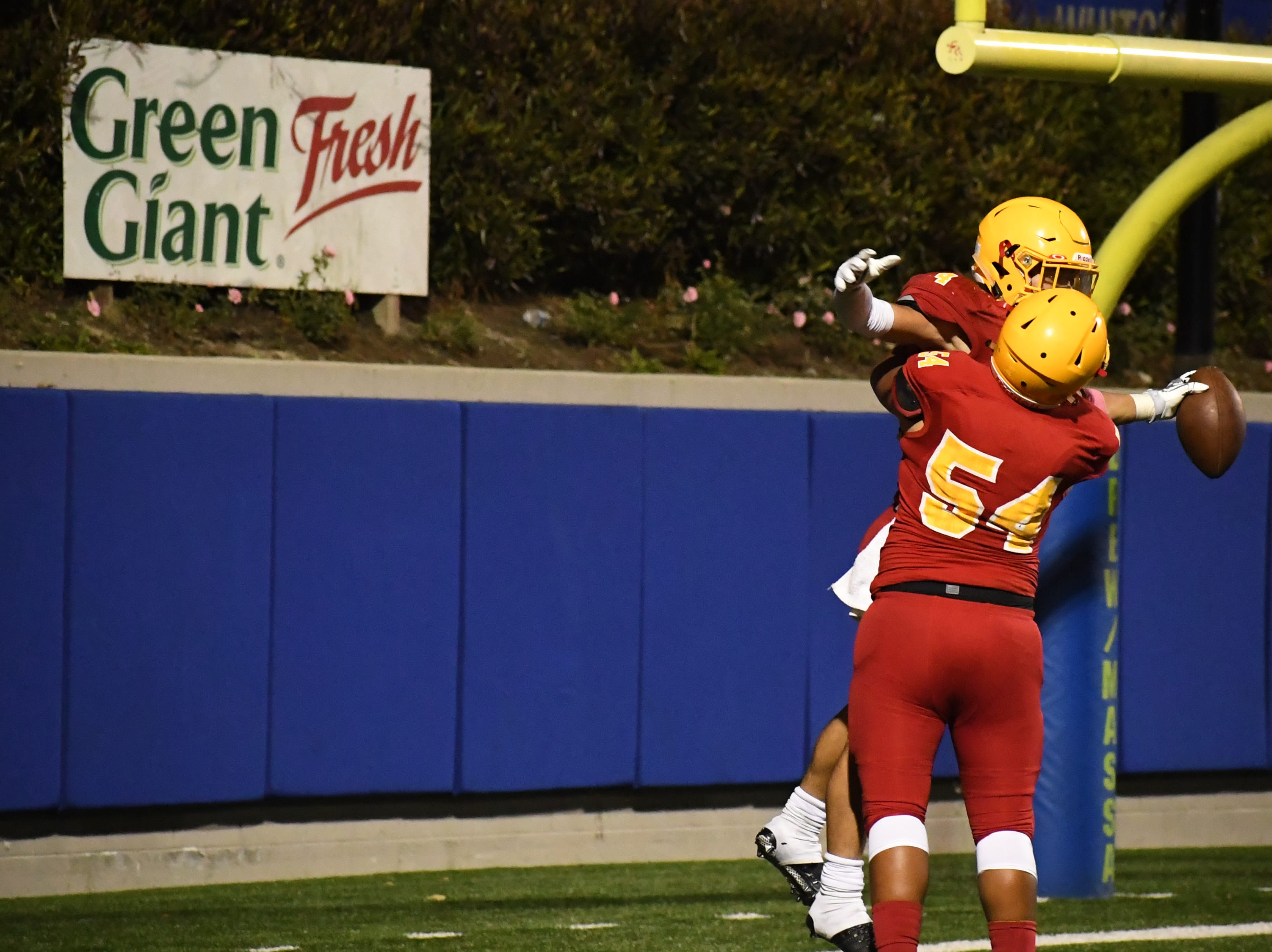 Palma junior running back Anthony Villegas (4) and lineman Oki Hautau (54) celebrate Villegas' 37-yard touchdown.