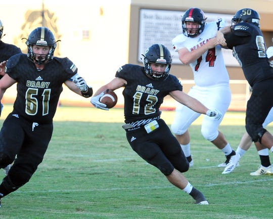 With Ryder Ross (51) along to block, Brady running back Ryan Decker (12) makes an offensive gain during the first quarter of their game against Ballinger on Friday, Aug. 31, 2018.