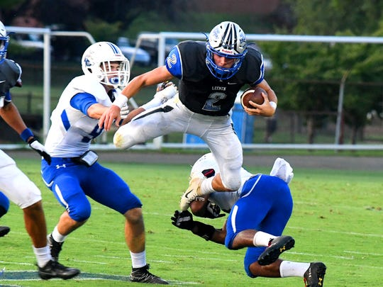 Robert E. Lee's William Dod is airborne with the ball after slipping out of the grasp of Rockbridge County's Jailik Lynch during a football game played in Staunton on Friday. August 31, 2018.
