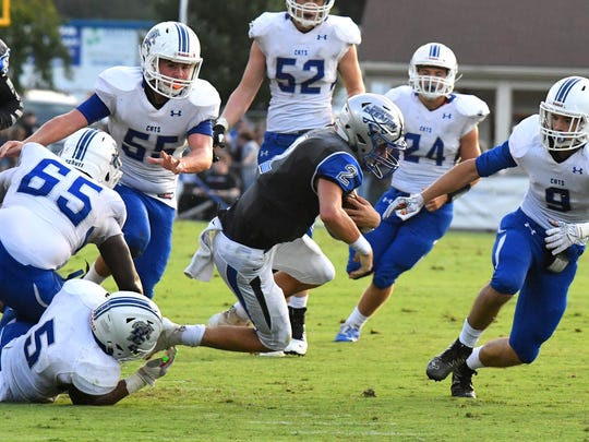 Robert E. Lee quarterback William Dod is tripped up and goes down with the ball after running it on a quarterback keep during a football game played in Staunton on Friday. August 31, 2018.