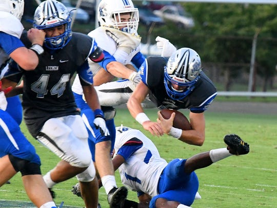 Robert E. Lee's William Dod has the ball as he flies overtop Rockbridge County's Jailik Lynch as he is tackled during a football game played in Staunton on Friday. August 31, 2018.