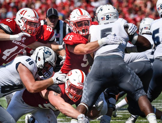 St. John's players Richard Carriveau, Nathan Brinker and Kyle Borgeson  join forces on defense to stop Rayshawn Graham of UW-Stout during the Saturday, Sept. 1, game at Clemens Stadium in Collegeville.