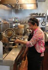 Kumaree Anderson has some fun in the kitchen of her Cedar City restaurant, Erawan Thai Cuisine.