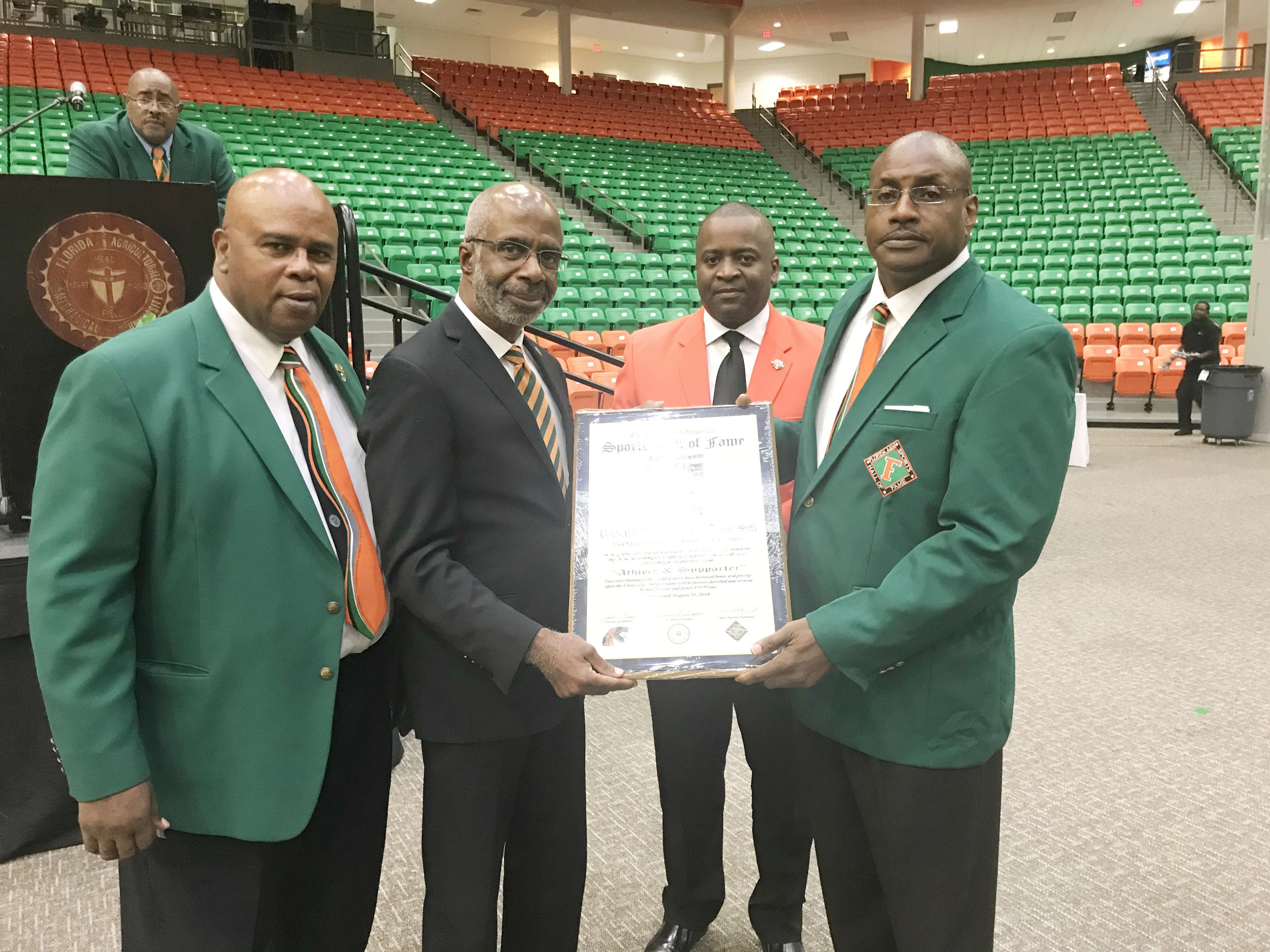 From left to right: Curtis Taylor, FAMU president Dr. Larry Robinson, FAMU National Alumni Association president Gregory Clark present Rick Clark with his Hall of Fame plaque.