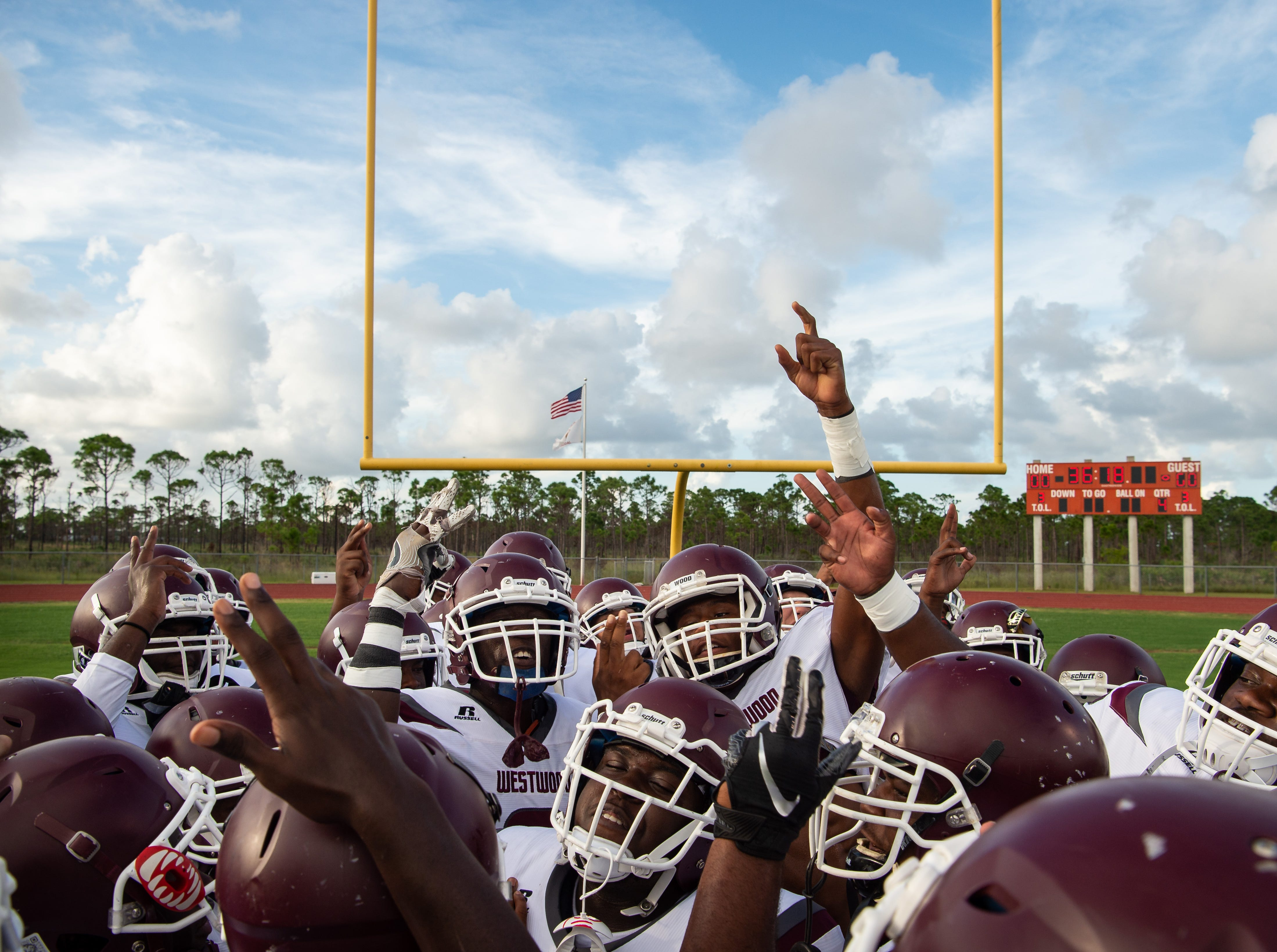 Fort Pierce Westwood's Willie Lewis (center) raises his arm and leads a chant for the team as they take the field to play Port St. Lucie during the high school football game Friday, Aug. 31, 2018, at Port St. Lucie High School.
