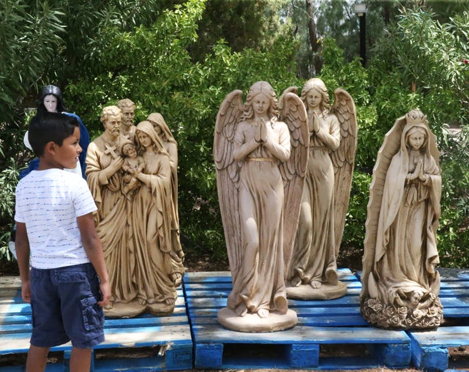 Kaleb Tucker, 6, of El Paso waits for his family to catch up amid a row of religious statuary at the entrance to the annual St. Anthony Seminary Bazaar at 4501 Hastings Drive Saturday. The annual Labor Day bazaar, now in its 54th year features food, games and live entertainment hosted on the grounds of the Franciscan Seminary, founded in 1931. It is the seminary's largest fundraising event of the year and continues Sunday and Monday from 11 a.m. to 10 p.m., said Fr. Francisco Rodriguez, a seminary priest.