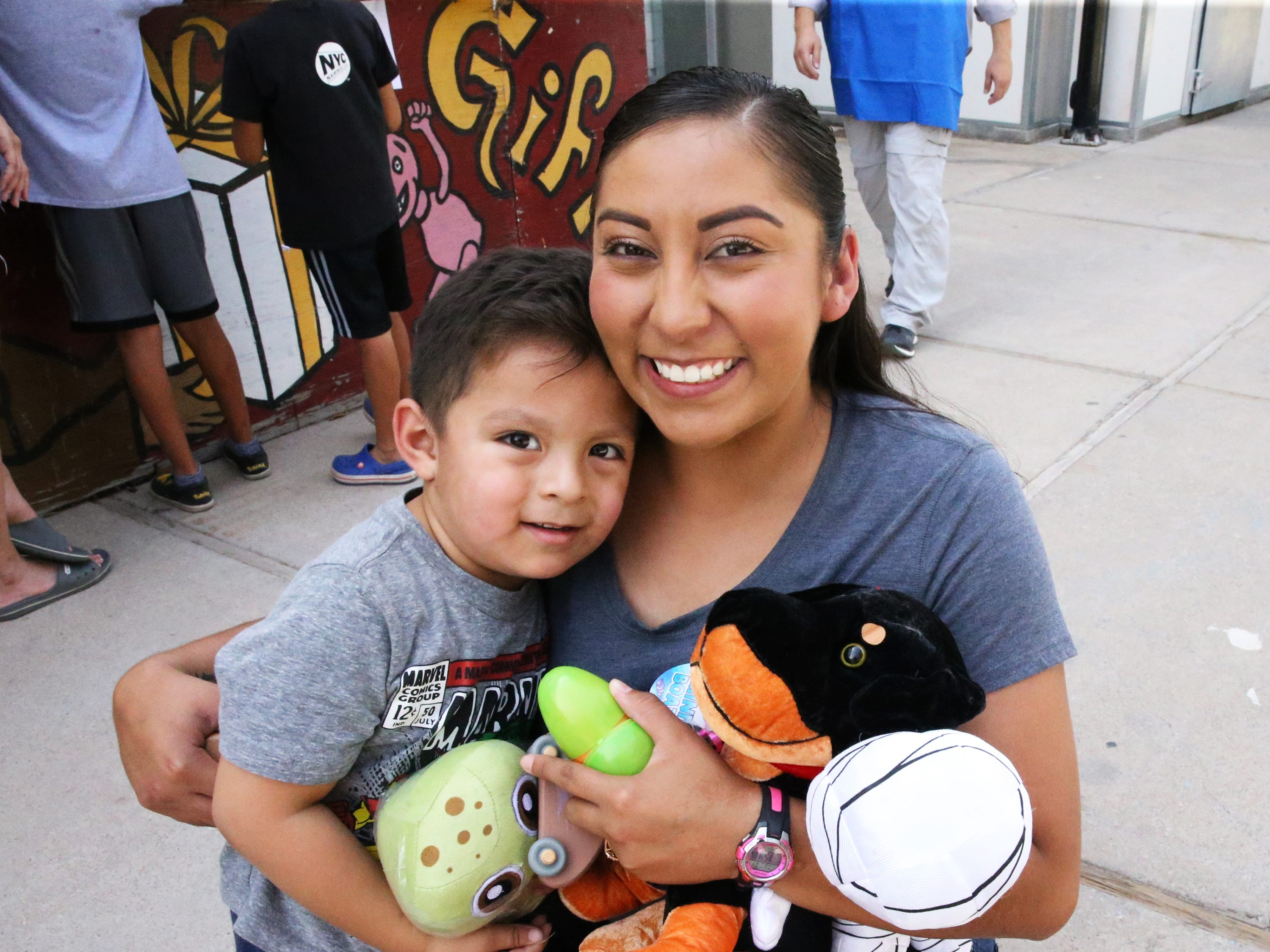 Joanna Hernandez and son, Anthony Hernandez with toys and stuffed animals the youngster won playing marbles, darts, boats and basketball at St. Anthony's Bazaar Saturday.