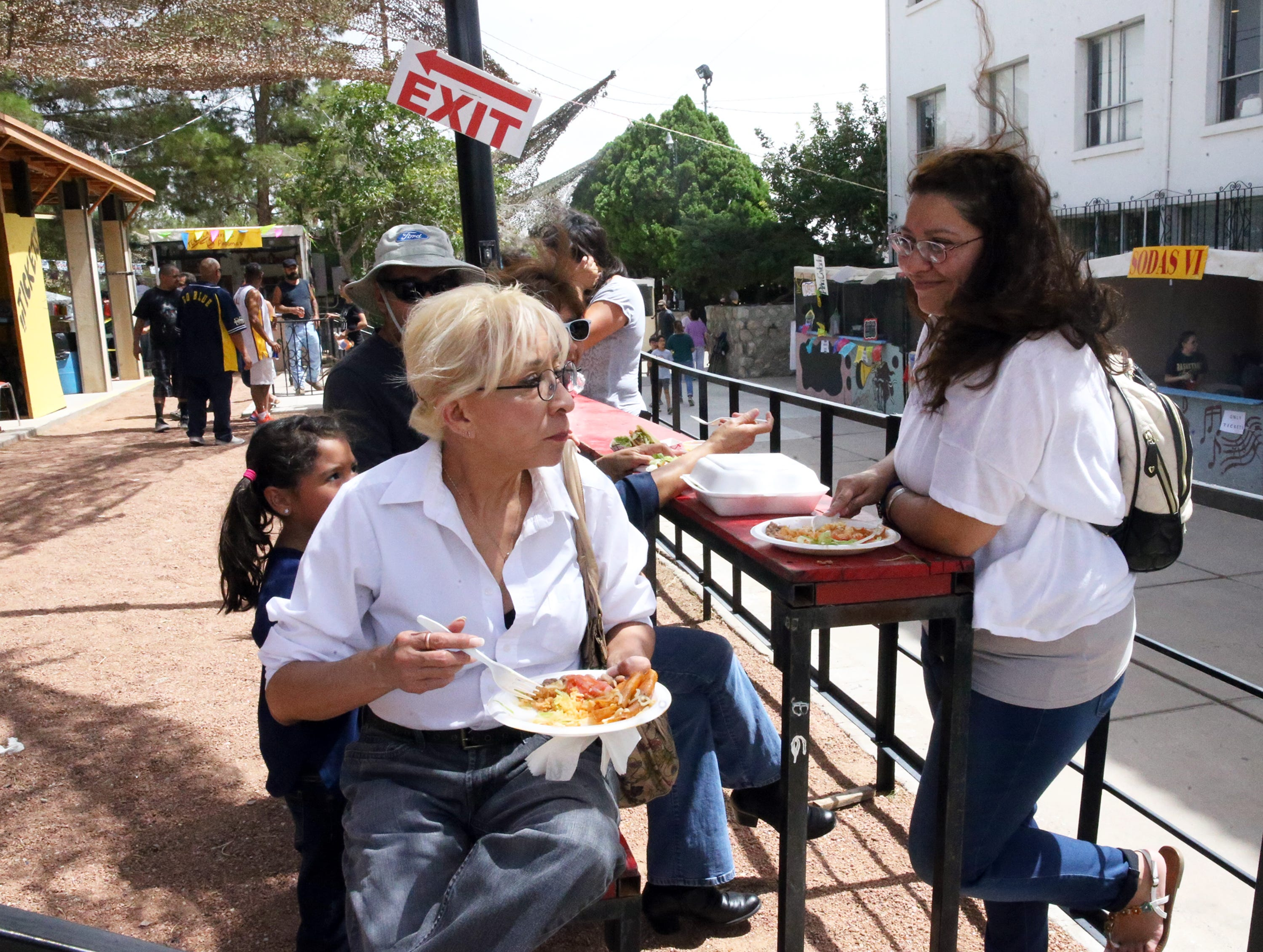 Gloria Espinosa, left, and Yvette Coffman, right, enjoy an enchilada plate at the 54th annual St. Anthony's Bazaar at 4501 Hastings Drive Saturday.