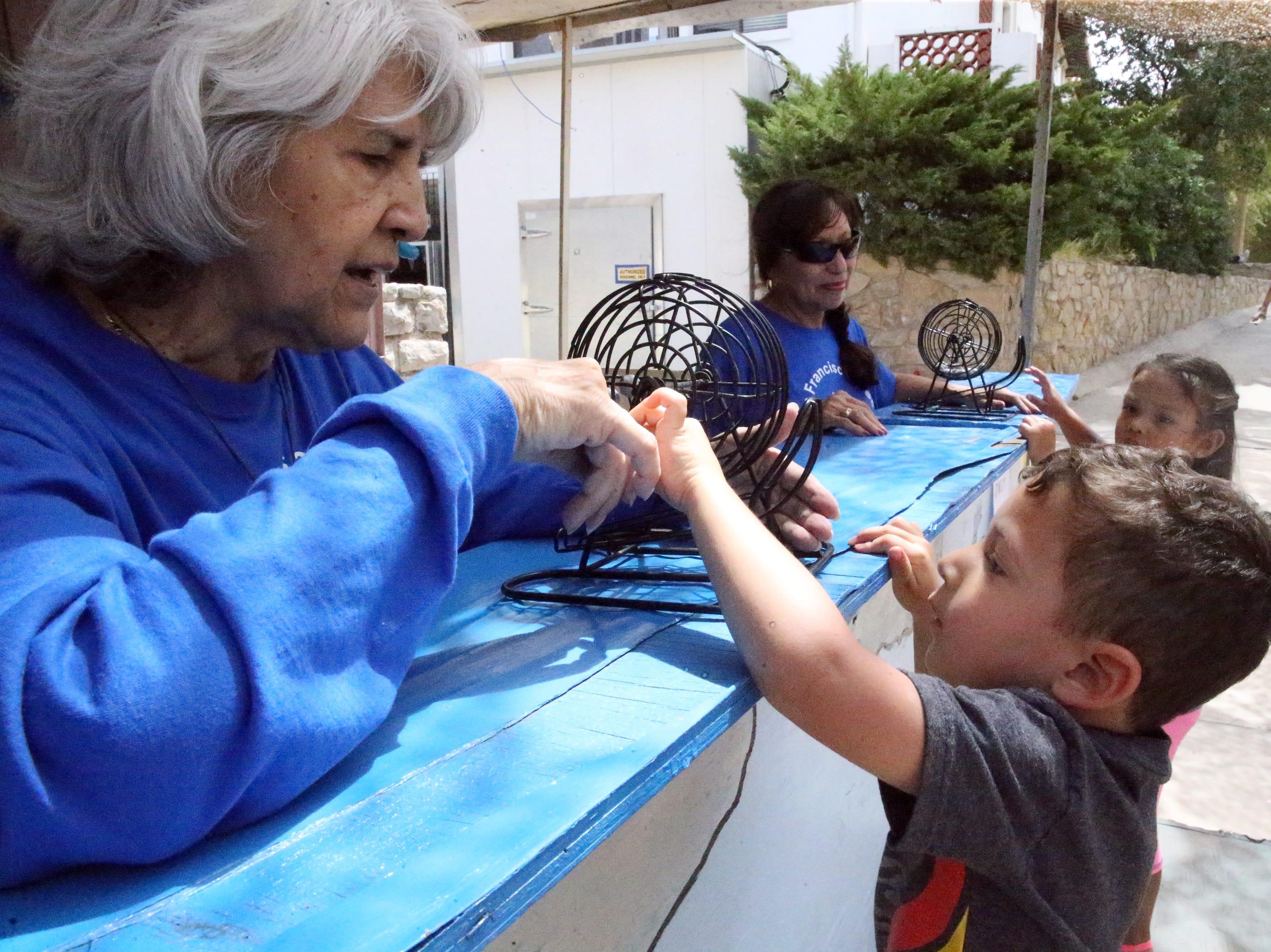 Ester Elixavide, left, helps Ryan Olivas, 4, with a tambola game Saturday.