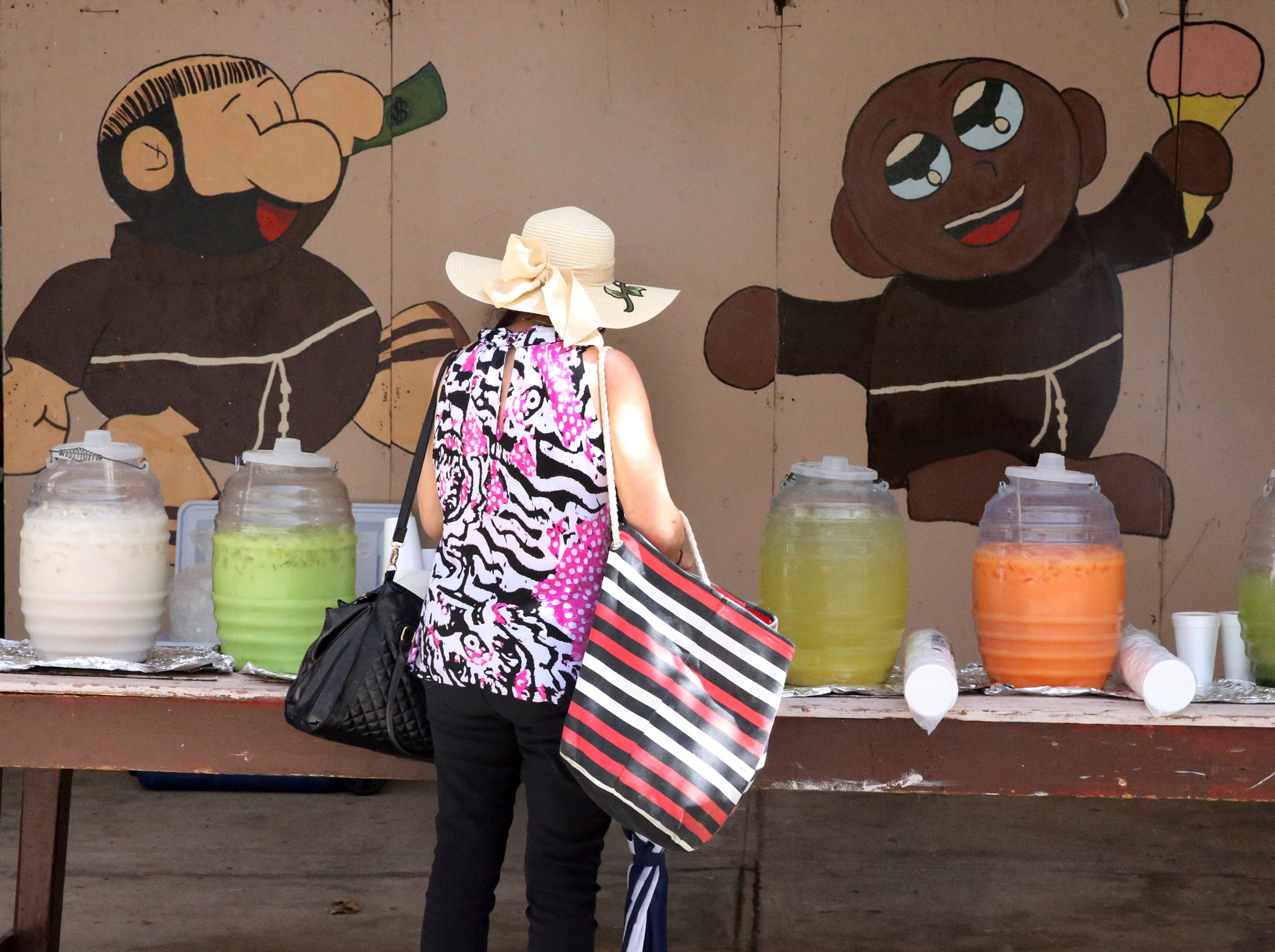 A woman stops by the aguas frescas, or fresh fruit water stand at the annual St. Anthony's Bazaar Saturday.