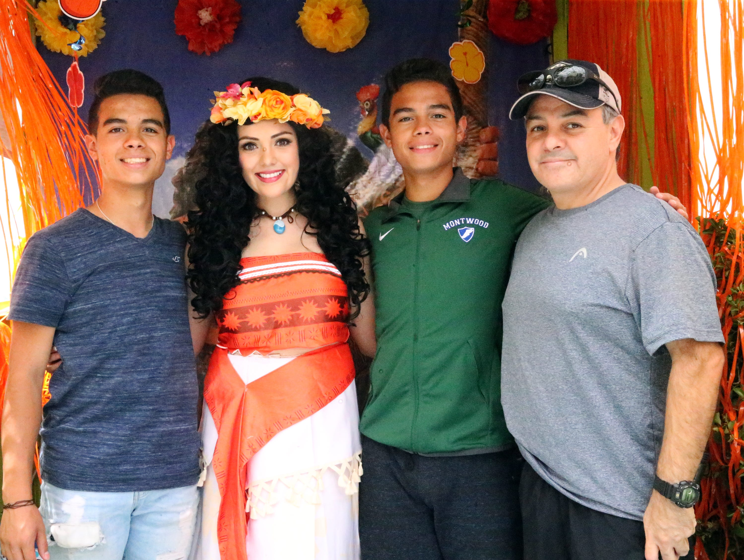 Izak Jimenez, left, his twin brother Juan Jimenez and their father, Juan Jimenez pose for a photo with Veronica Varela at the Princess Moana makeovers booth Saturday.