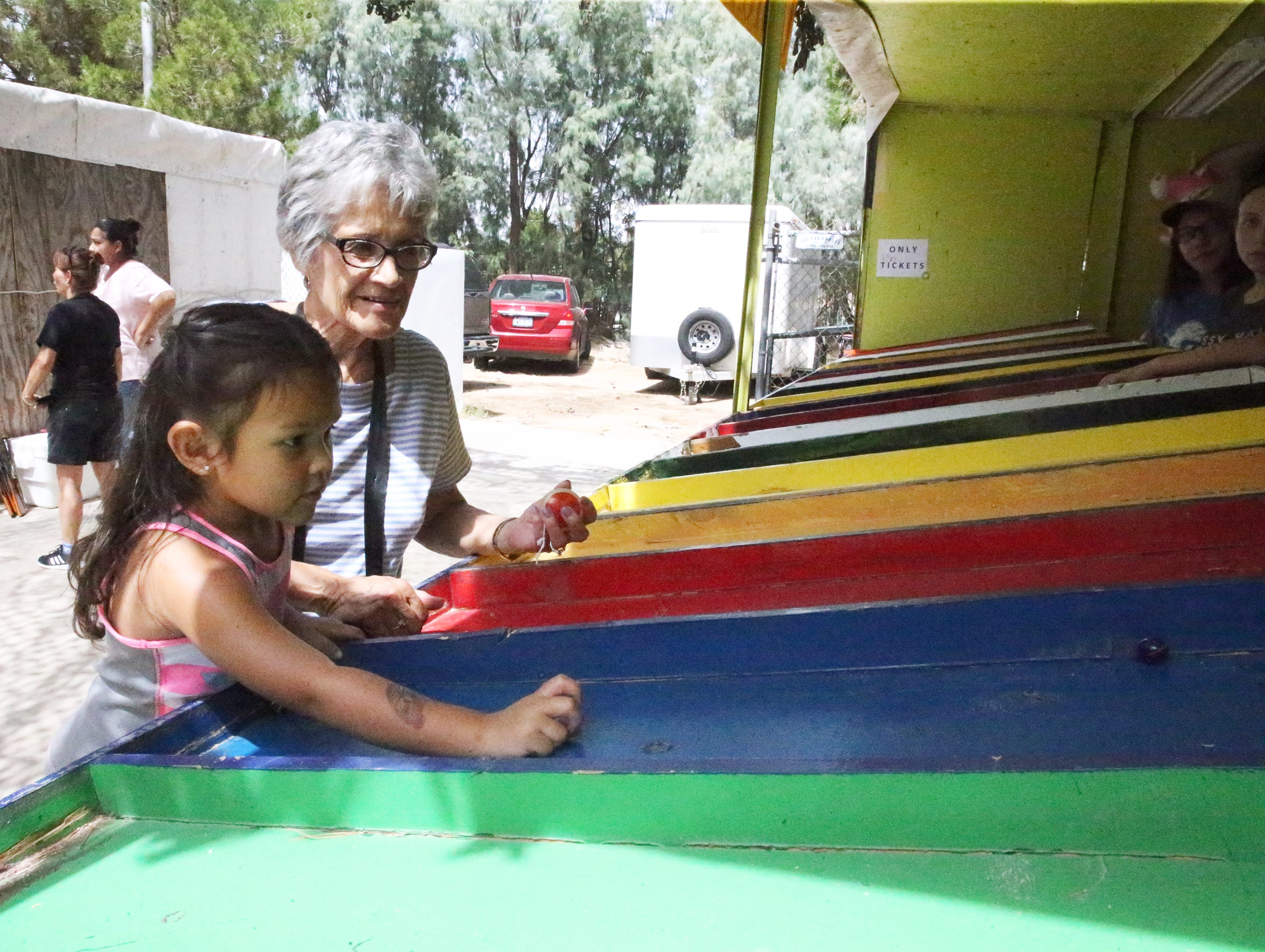 Camila Olivas, 4, tries her hand at marbles with grandmother Elia Olivas Saturday.